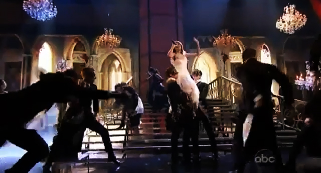 Taylor Swift lifted up by the masked men in black suits.